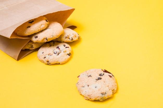 Koekjes in een papieren zak op een gele achtergrond kopieer ruimte gezonde snack