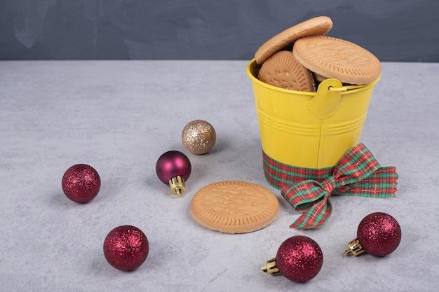 Koekjes in emmer versierd met touw en kerstballen op witte tafel.