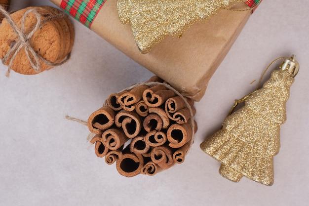 Koekjes in kabel met pijpjes kaneel en kerstmisstuk speelgoed op witte oppervlakte