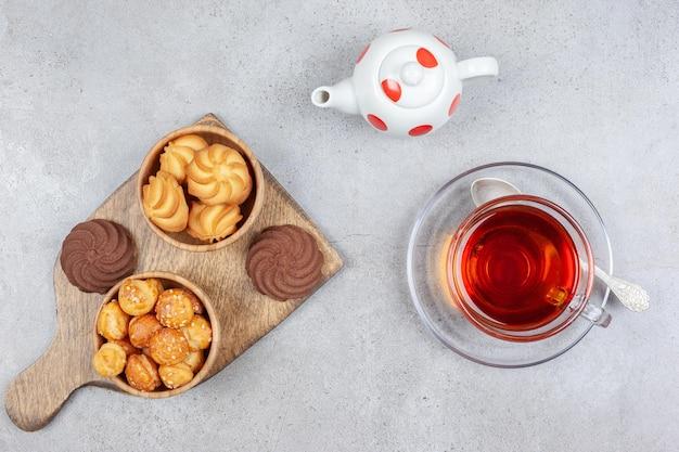 Koekjes in kommen en op houten bord, met een kopje thee en een theepotje op marmeren ondergrond