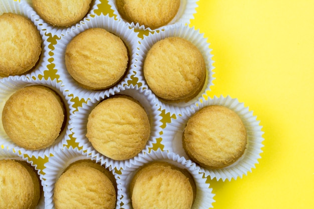 Koekjes in papiermanden op gele achtergrond