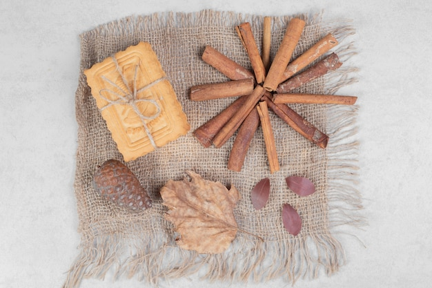 Koekjes in touw met kaneelstokjes, blad en dennenappel op jute. hoge kwaliteit foto