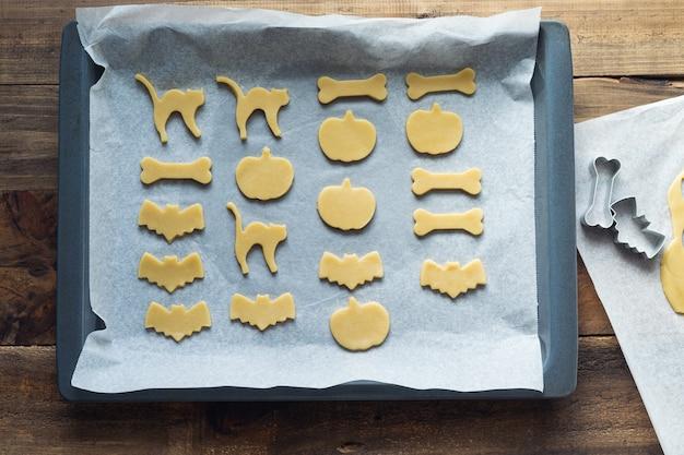Koekjes in verschillende vormen voor halloween op een bakplaat. koekjes gesneden voor het bakken. ruimte kopiëren.