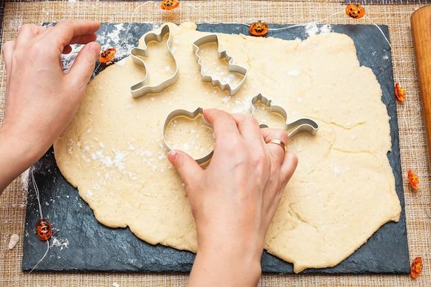 Koekjes maken voor halloween. een vrouw snijdt koekjes uit het deeg in de vorm van pompoen, kat, spook en vleermuis.