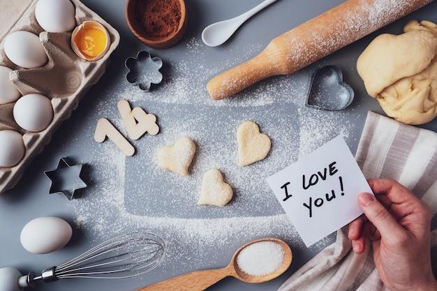 Koekjes maken voor valentijnsdag, plat leggen, bovenaanzicht, kopieerruimte. verschillende ingrediënten, deegroller, deeg, eieren, nummers 14, garde op een grijze achtergrond, lay-out op een grijze achtergrond.
