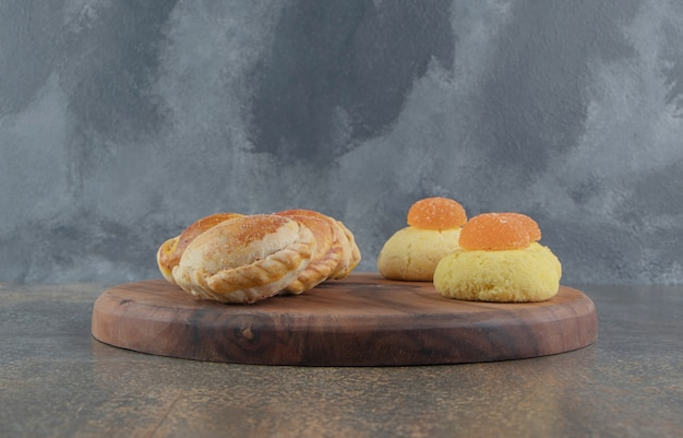 Koekjes, marmelades en kleine broodjes op een bord