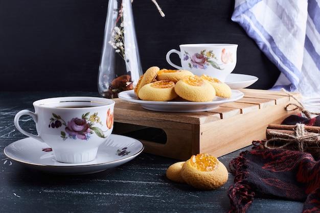 Koekjes met abrikozenconfituur geserveerd met thee.