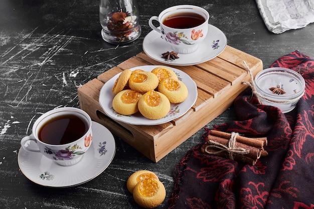 Koekjes met abrikozenconfituur met twee kopjes thee.