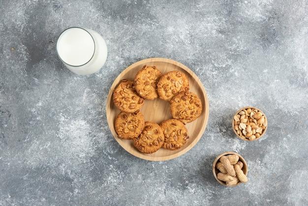 Koekjes met biologische pinda's en glas melk op marmeren tafel.