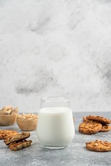 Koekjes met biologische pinda's en honing met glas melk op marmeren tafel.