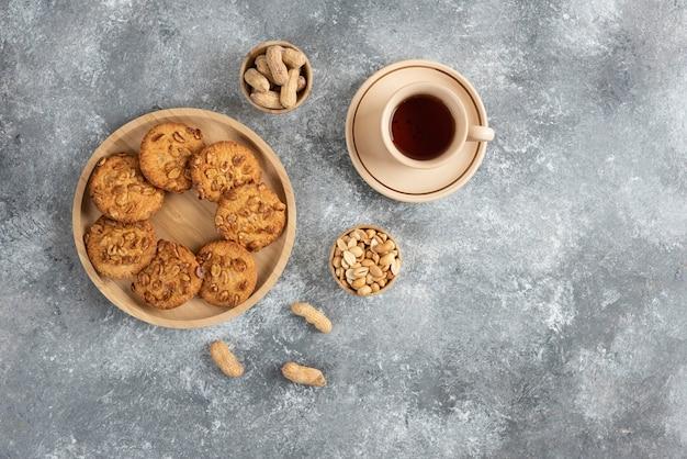 Koekjes met biologische pinda's en honing op een houten bord met kopje thee.