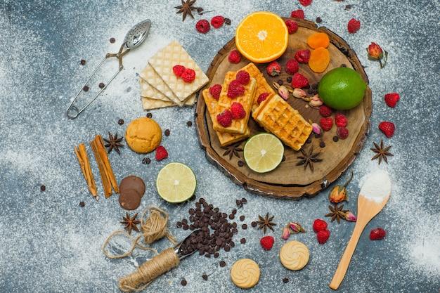 Koekjes met bloem, kruiden, fruit, specerijen, choco, zeef bovenaanzicht op houten bord en stucwerk achtergrond
