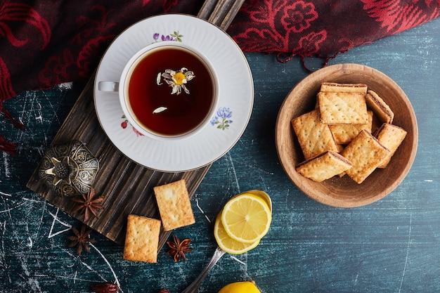 Koekjes met cacao vulling in een houten beker met een kopje thee, bovenaanzicht.