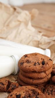 Koekjes met chocoladedruppels op ambachtelijk papier en flessen melk. natuurlijke handgemaakte biologische slangen voor een gezond ontbijt. verticale foto