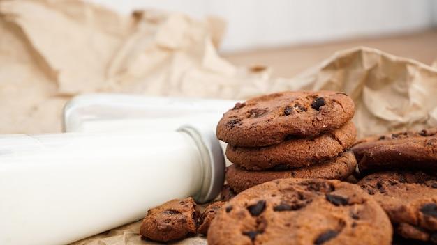 Koekjes met chocoladedruppels op ambachtelijk papier en flessen melk. natuurlijke handgemaakte biologische slangen voor een gezond ontbijt
