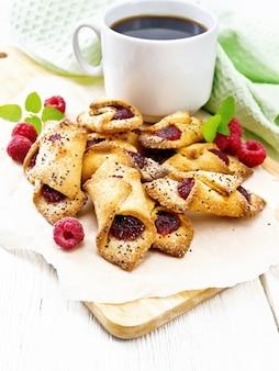 Koekjes met frambozenjam, bessen en munt op perkament op een plank, een kopje koffie en servet op de achtergrond van een licht houten bord