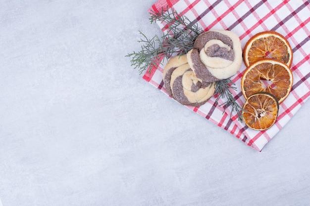 Koekjes met gedroogde sinaasappel op tafellaken en pijnboomtak.