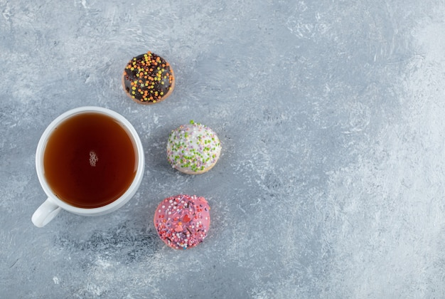 Koekjes met hagelslag en kopje thee op marmeren tafel.