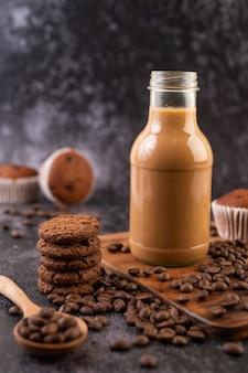 Koekjes met koffiebonen geplaatst op een houten plaat.