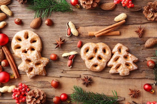 Koekjes met noten, kruiden en takjes kerstboom op rustieke houten ondergrond