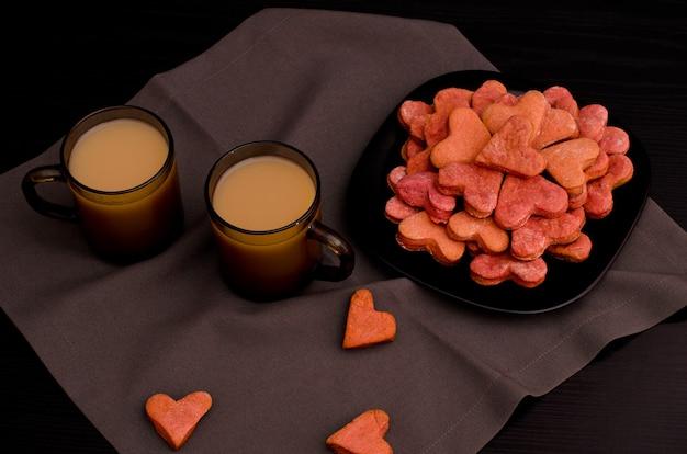 Koekjes met rode hartvormige, twee mokken koffie met melk, valentijnsdag