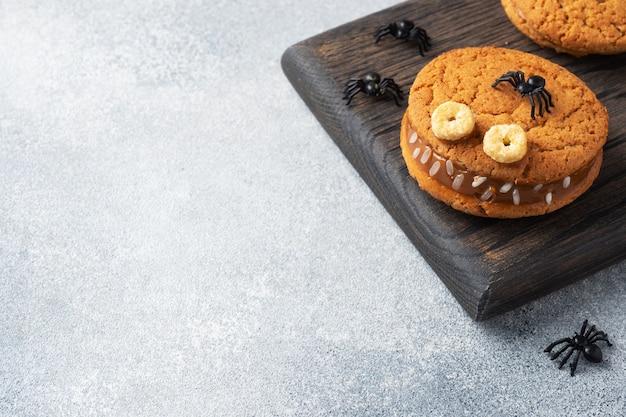 Koekjes met roompasta in de vorm van monsters voor halloween-viering. grappige zelfgemaakte gezichten gemaakt van havermoutkoekjes en gekookte gecondenseerde melk. kopieer ruimte