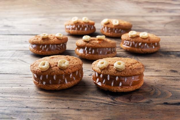 Koekjes met roompasta in de vorm van monsters voor halloween-viering. grappige zelfgemaakte gezichten gemaakt van havermoutkoekjes en gekookte gecondenseerde melk.