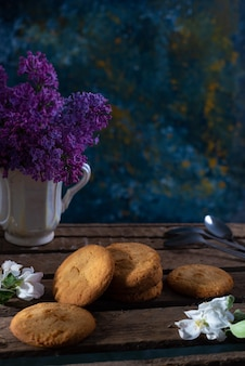 Koekjes met rustieke bloemenvaas op de achtergrond op houten tafel