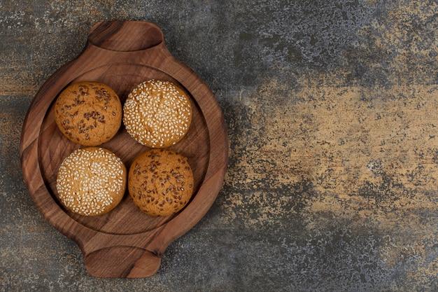 Koekjes met sesamzaadjes en chocoladestukjes op een houten bord.