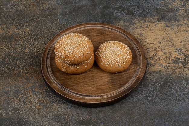 Koekjes met sesamzaadjes op een houten bord.