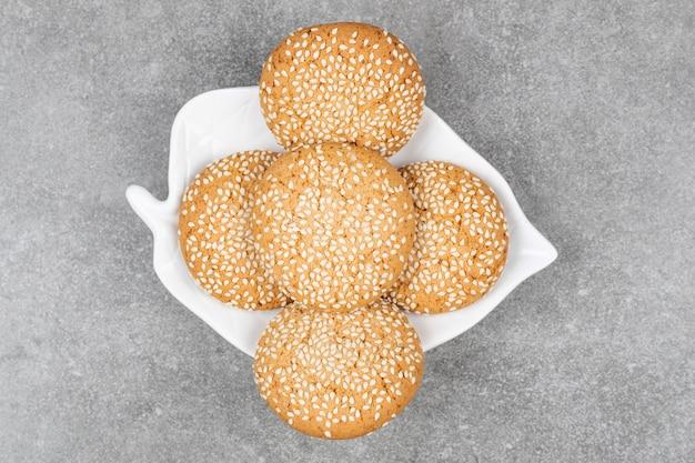 Koekjes met sesamzaadjes op witte plaat