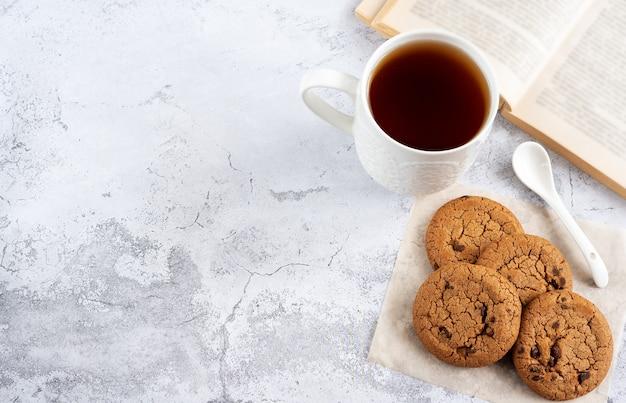 Koekjes met stukjes chocolade, thee en een open boek op een lichte achtergrond, bovenaanzicht
