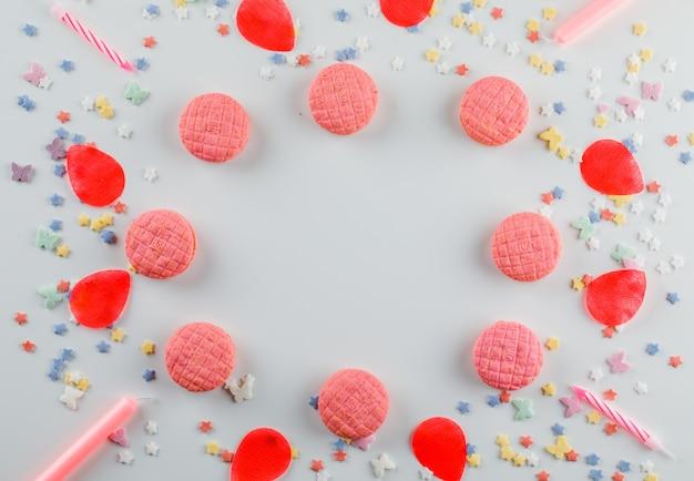 Koekjes met suiker hagelslag, kaarsen, bloemblaadjes op witte tafel