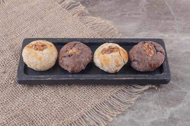 Koekjes met toppings van walnoten op een kleine, zwarte schaal op marmer