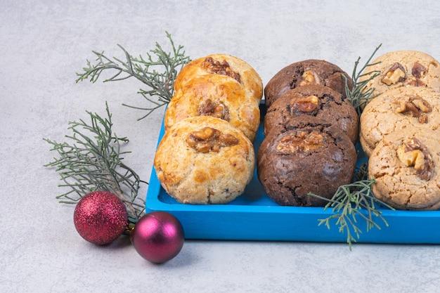 Koekjes met walnoot op een bord naast kerstballen en brunch, op het marmer.