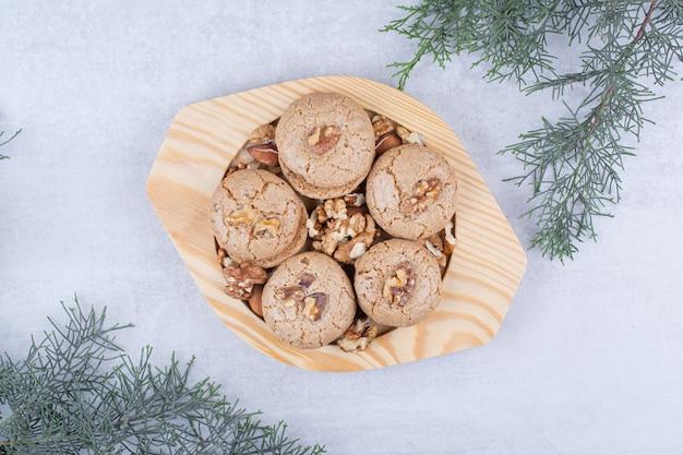 Koekjes met walnootpitten op houten plaat.