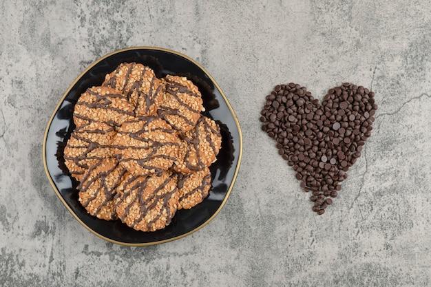 Koekjes met zaden op zwarte plaat met stapel van dalingschocolade.