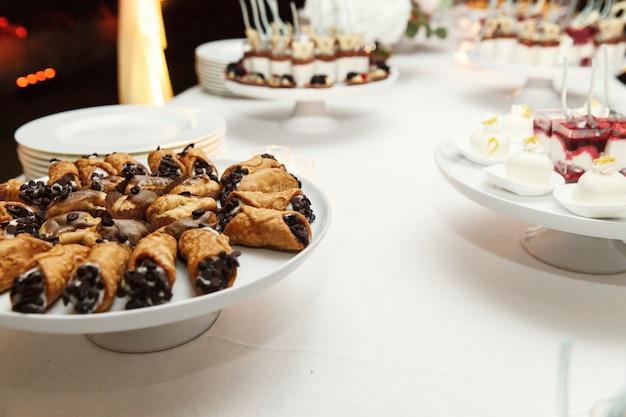 Koekjes met zwarte chocolade die op witte schotel wordt gediend