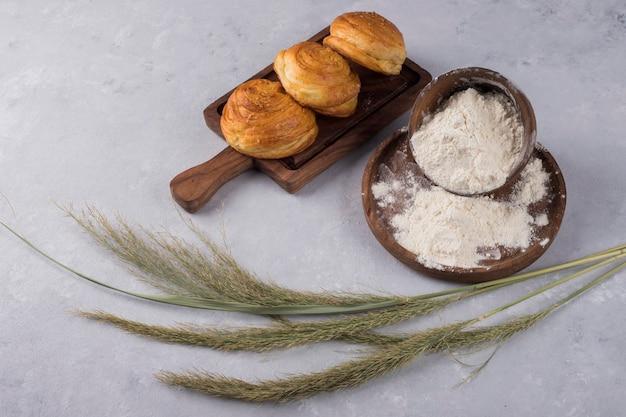 Koekjes of broodjes met bloem op een houten schotel die met kruiden wordt gediend
