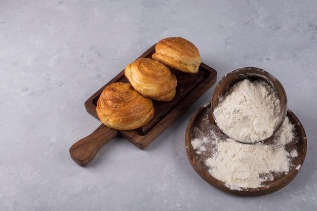 Koekjes of broodjes met bloem op een houten schotel