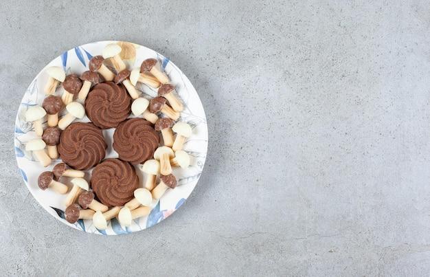 Koekjes omgeven door chocoladepaddestoelen op een bord op marmeren achtergrond.