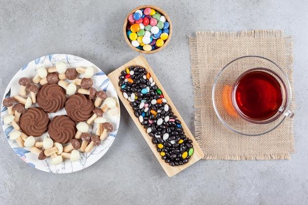 Koekjes omgeven door chocoladepaddestoelen op een bord, snoepjes in een kom en een dienblad met een kopje thee op een marmeren oppervlak.