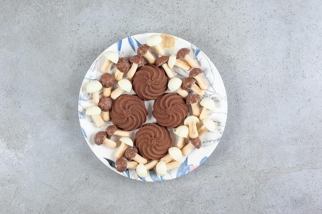 Koekjes omringd door chocoladepaddestoelen op een plaat op marmeren achtergrond. hoge kwaliteit foto