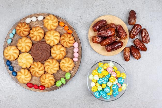 Koekjes omringd door snoepjes op een houten bord naast een kom met snoepjes en dadels op een marmeren oppervlak.