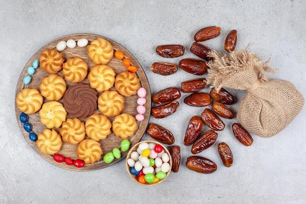 Koekjes omringd met snoepjes op een houten bord naast een kom met snoep, een zak en verspreide dadels op een marmeren oppervlak.