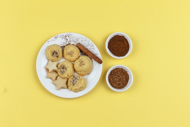 Koekjes op een bord met koffie, kaneelstokje op een gele achtergrond