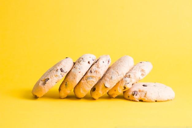 Koekjes op een gele ondergrond, koekjes met stukjes chocolade en rode bosbessen