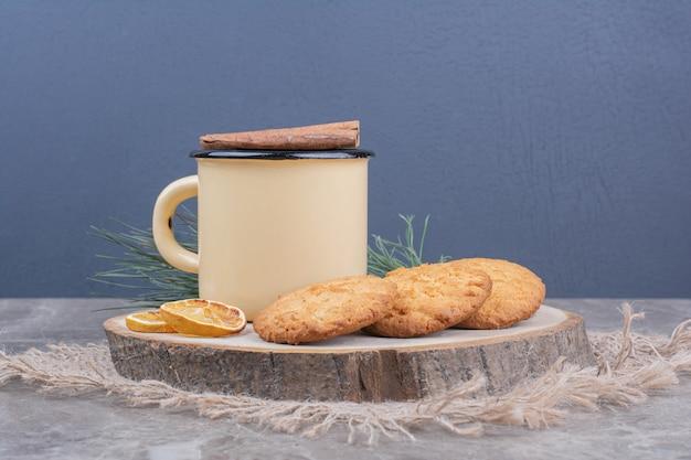 Koekjes op een houten bord met een kopje thee eromheen.