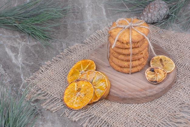 Koekjes op een houten bord met stukjes sinaasappel rond.