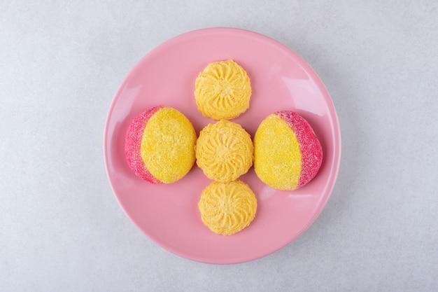Koekjes op een roze bord, op het marmer.